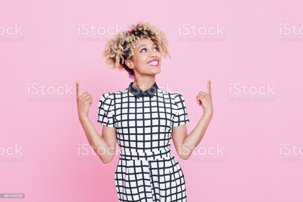 Beautiful afro american young woman pointing at copy space Studio portrait of happy afro american young woman pointing with index fingers at copy space. Pink background. 20-24 Years Stock Photo