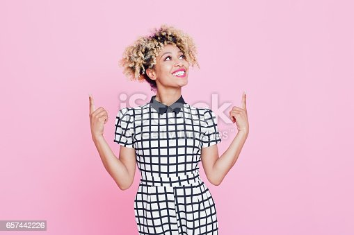 istock Beautiful afro american young woman pointing at copy space 657442226