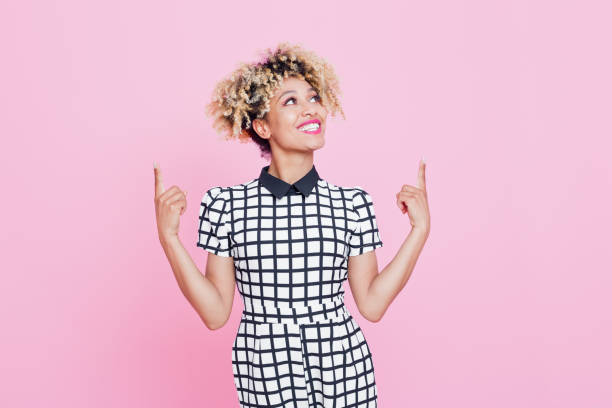 beautiful afro american young woman pointing at copy space - finger point stock photos and pictures