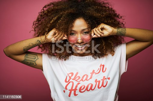 Beautiful afro Caribbean young woman in summer clothes against pink background.