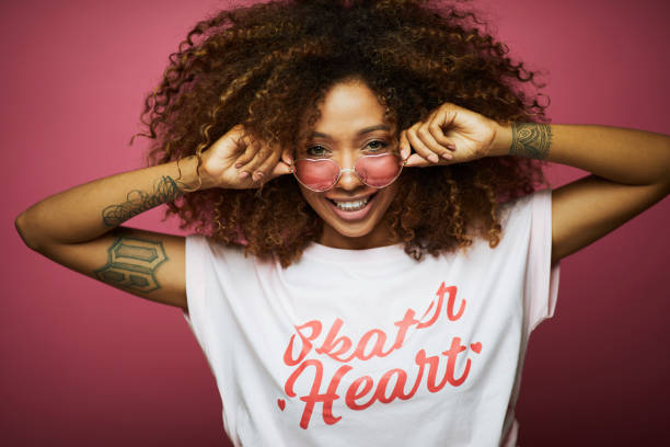 Beautiful afro Caribbean young woman in summer clothes against pink background. Beautiful afro Caribbean young woman in summer clothes against pink background. pop musician stock pictures, royalty-free photos & images