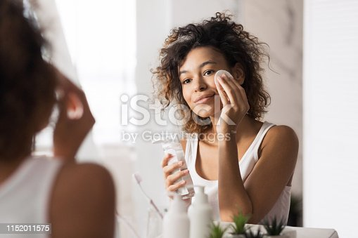 Young afro-american woman cleaning face with cotton pad looking in mirror at bathroom