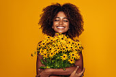 istock Beautiful afro woman with bunch of flowers 1287401050