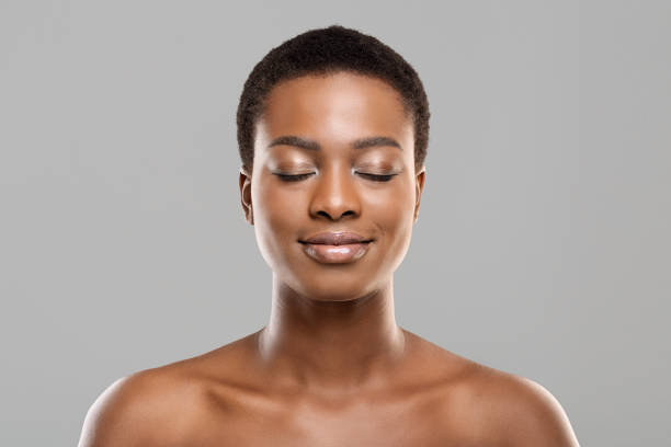 Beautiful afro woman with closed eyes, natural makeup and perfect skin stock photo