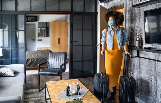 Beautiful afro woman with protective face mask arriving in hotel room
