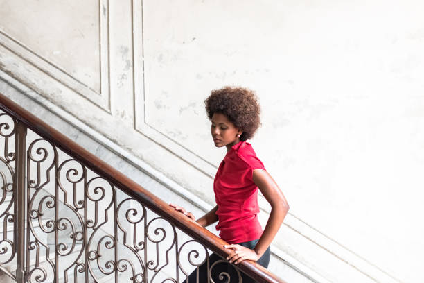 beautiful afro-caribbean woman on stairway in old house in Havana beautiful afro-caribbean woman going up stairway in old house in Havana afro caribbean ethnicity stock pictures, royalty-free photos & images