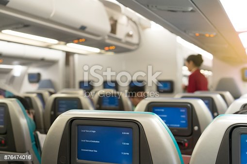 823006998 istock photo Beautiful air hostess or fight attendant waiting for service passengers on board in interior aircraft. Fight attendant with map time on monitor. 876474016