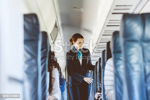 Beautiful air stewardess inside an airplane.