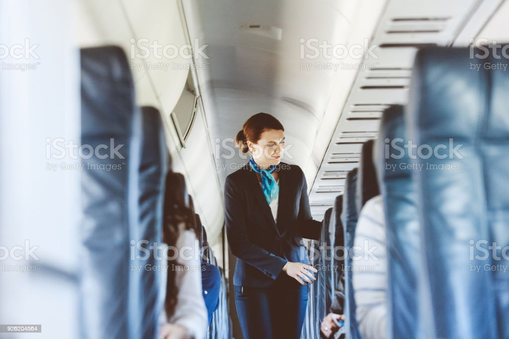 Beautiful air stewardess inside an airplane stock photo