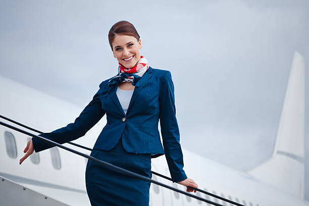 Beautiful air stewardess Outdoor portrait of a beautiful flight attendant standing on the aircraft stairs and smiling at the camera. cabin crew stock pictures, royalty-free photos & images