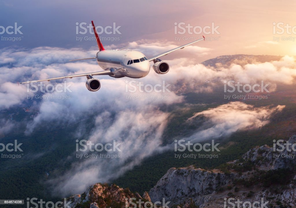 Beautiful airplane is flying over low clouds at sunset. Landscape with passenger airplane, rocks, forest, blue sky with orange sunlight in dusk. Passenger aircraft. Business travel. Commercial plane stock photo