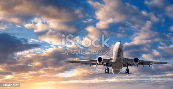 816320512 istock photo Beautiful airplane. Landscape with white passenger airplane is flying in the blue sky with clouds at colorful sunset. Travel background. Passenger airliner. Business trip. Commercial aircraft 816320452