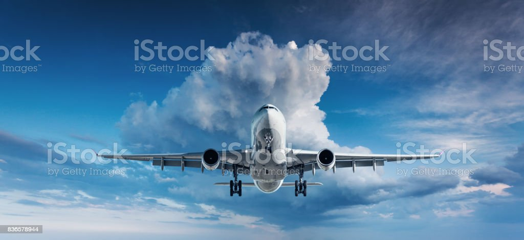 Beautiful airplane. Landscape with white passenger airplane is flying in the blue sky with clouds at overcast day. Travel background. Passenger airliner. Business trip. Commercial plane. Aircraft stock photo