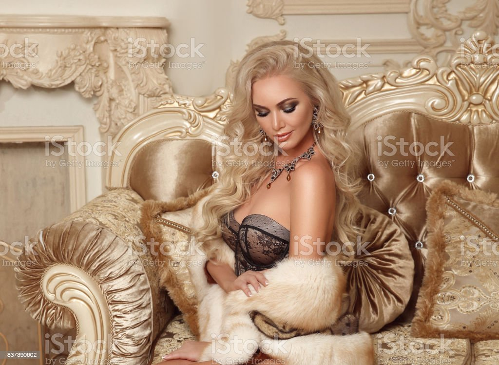 Beautiful alluring blond woman in sexy lingerie and fur coat posing on royal sofa with pillows in luxurious modern interior. Beauty glamour fashion style photo portrait. stock photo