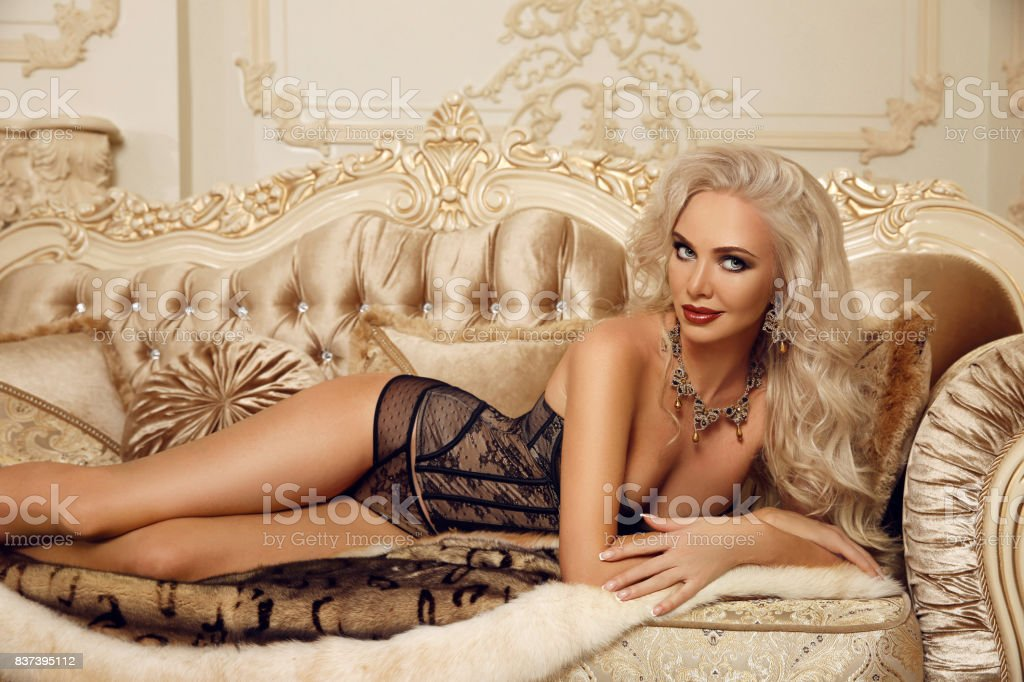 8262f65b6 Linda mulher loira sedutora lingerie sexy deitada no sofá real no interior  de luxo moderno.