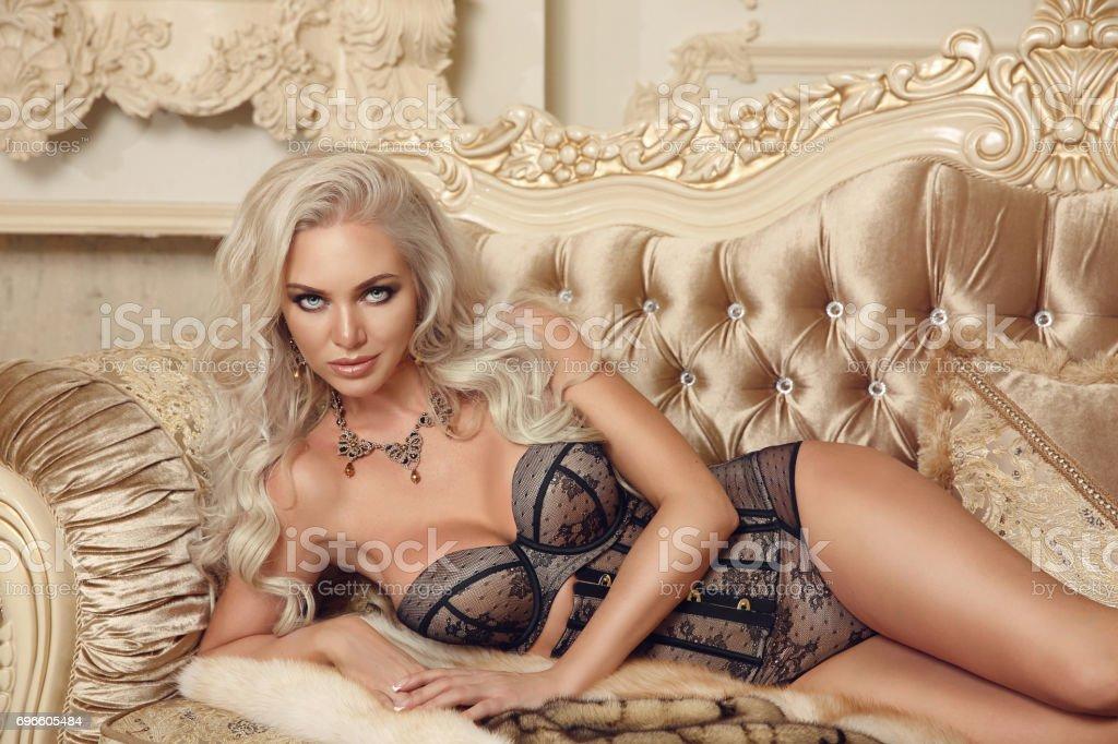9a9cbda3717 Vackra lockande ung kvinna i sexiga underkläder liggande på royal soffa i  lyx modern interiör.