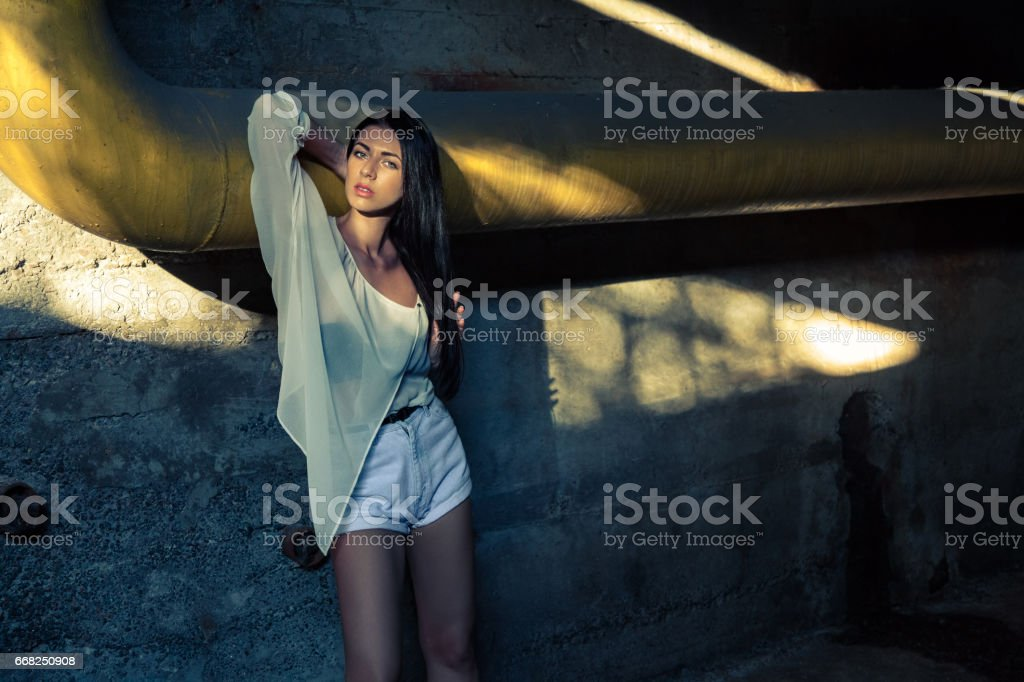 Beautiful alone girl and abandoned sewerage underground with ray of sunshine. foto stock royalty-free