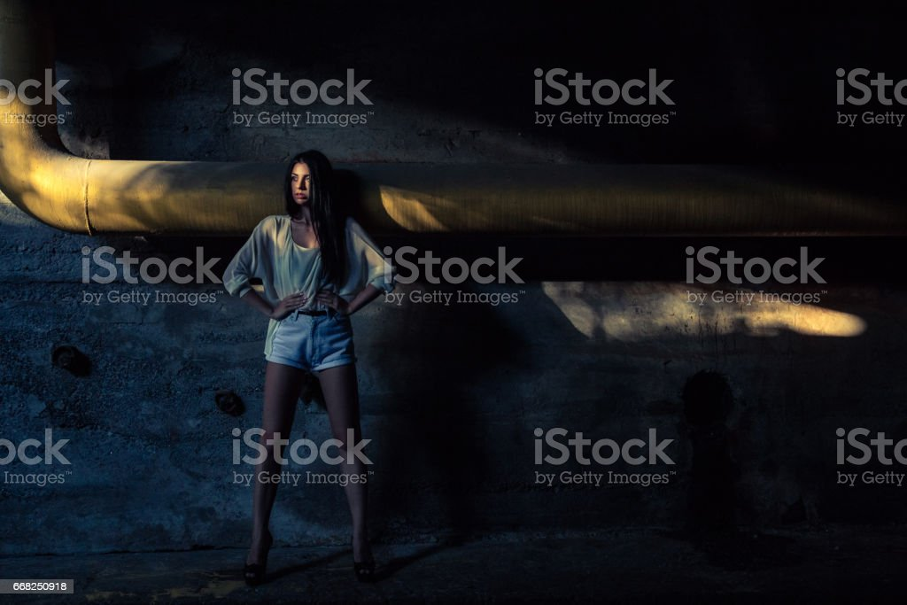 Beautiful alone girl and abandoned sewerage underground with ray of sunshine. foto stock royalty-free