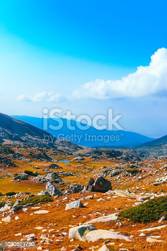istock Beautiful alpine high mountains peaks, blue sky background. Amazing Mountain hiking paradise landscape, autumn, yellow grass. 1030521780