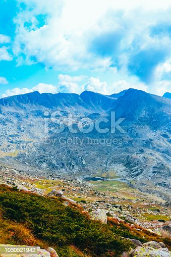 istock Beautiful alpine high mountains peaks, blue sky background. Amazing Mountain hiking paradise landscape, autumn, yellow grass. 1030521942