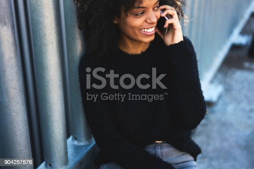 istock Beautiful american young woman calling to someone having pleasure conversation, hipster girl having talking via smartphone call with her friends during free time sitting outdoors 904257576
