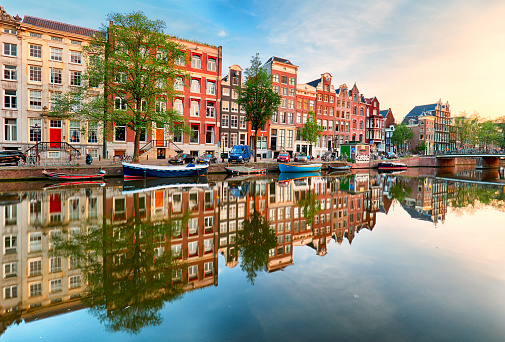 Beautiful Amsterdam sunset. Typical old dutch houses on the bridge and canals in spring, Netherlands