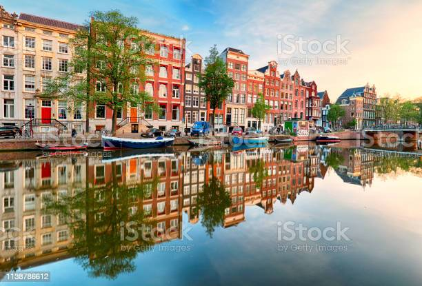 Photo of Beautiful Amsterdam sunset. Typical old dutch houses on the bridge and canals in spring, Netherlands