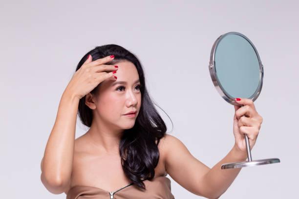 Schöne und Alterung Asiatin Gedanken über Falten und Beauty-Behandlung für ihre Hautpflege mit Spiegel. – Foto