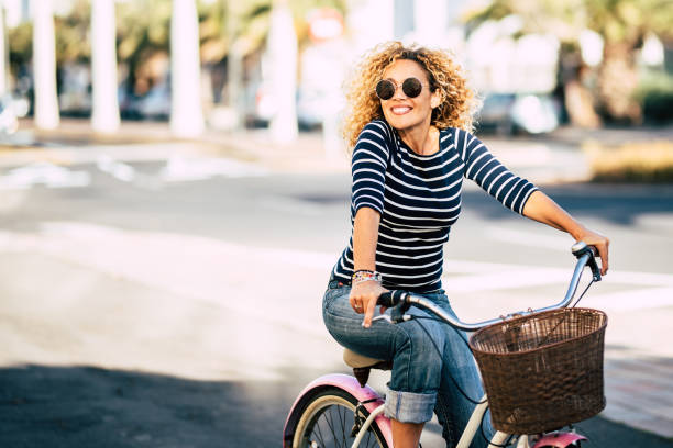 Beautiful and cheerful adult young woman enjoy bike ride in sunny urban outdoor leisure activity in the city - happy people portrait - trendy female outside having fun stock photo