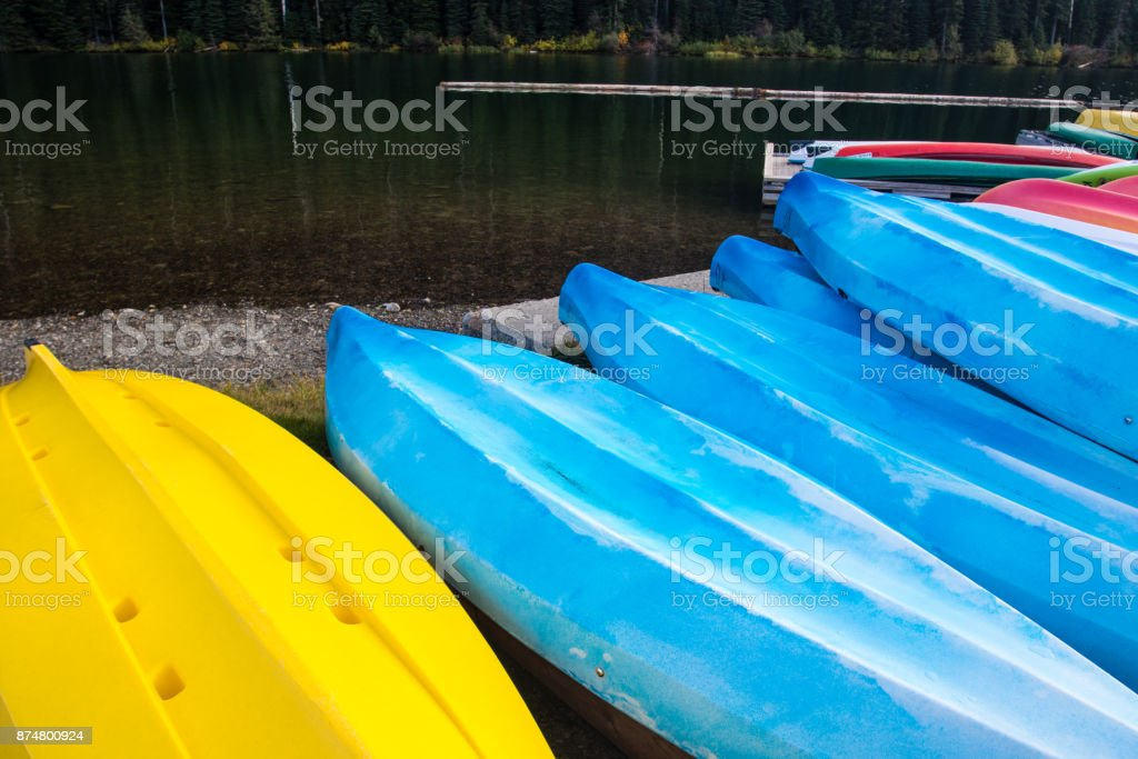 Beautiful and colorful kayaks in rows on a lake stock photo