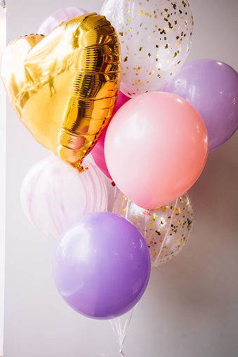 Beautiful and colourful (golden, pink, purple) festive balloons with a golden heart-shaped balloon on the grey wall background