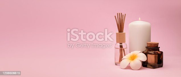 Beautiful and concise spa composition with a candle, frangipani flower, oil bottle and aroma diffuser on pink background. Copy space.