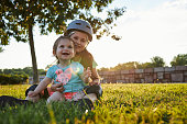 Beautiful and cheerful young girl with protective helmet embracing her baby sibling, a sister, enjoying the time at a park.