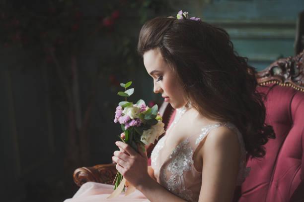 Hermoso y elegante peinado de la boda. Joven novia sentada - foto de stock