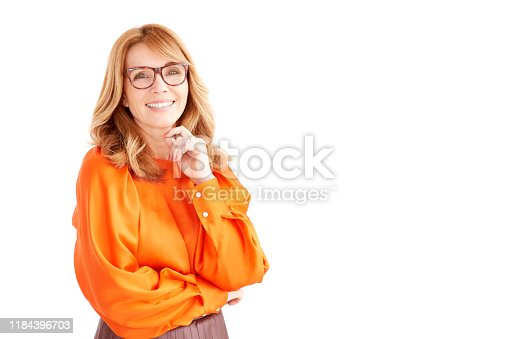 Portrait shot of happy middle aged woman with toothy smile standing at isolated white background and looking at camera. Copy space.