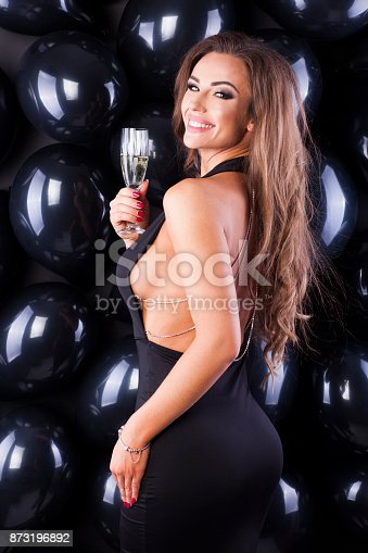 579443552istockphoto Beautiful and elegant woman with balloons and champagne ready for New Years Eve! 873196892