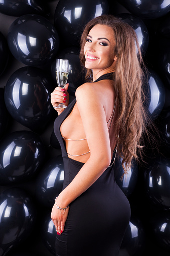 579443552 istock photo Beautiful and elegant woman with balloons and champagne ready for New Years Eve! 873196892