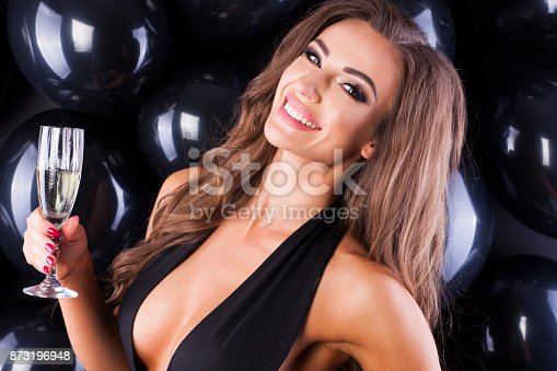 579443552istockphoto Beautiful and elegant woman with balloons and champagne ready for New Years Eve! 873196948
