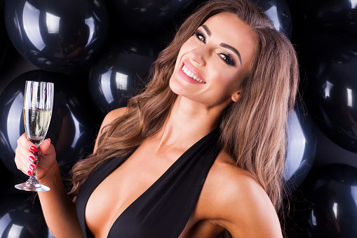 579443552 istock photo Beautiful and elegant woman with balloons and champagne ready for New Years Eve! 873196948