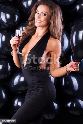 579443552istockphoto Beautiful and elegant woman with balloons and champagne ready for New Years Eve! 873197014