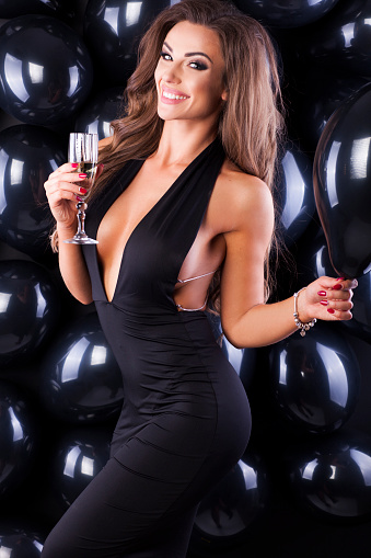 579443552 istock photo Beautiful and elegant woman with balloons and champagne ready for New Years Eve! 873197014