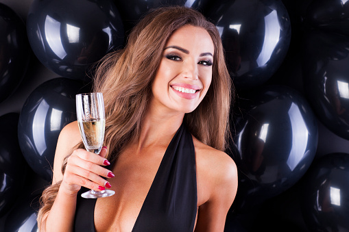 579443552 istock photo Beautiful and elegant woman with balloons and champagne ready for New Years Eve! 873197028