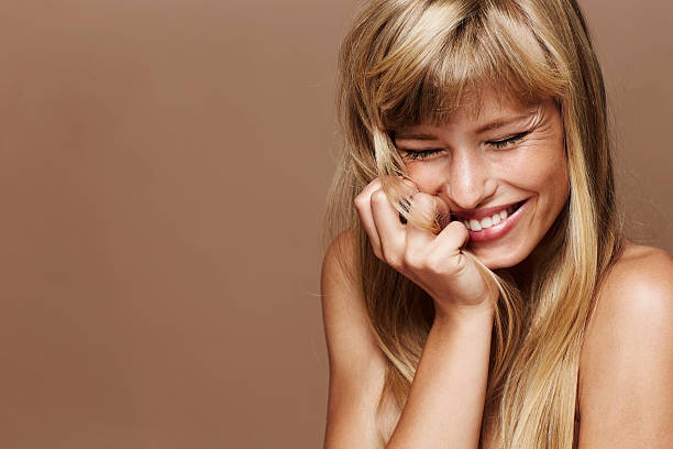 Beautiful and excited blond woman Gorgeous blond woman laughing in studio hand in hair stock pictures, royalty-free photos & images