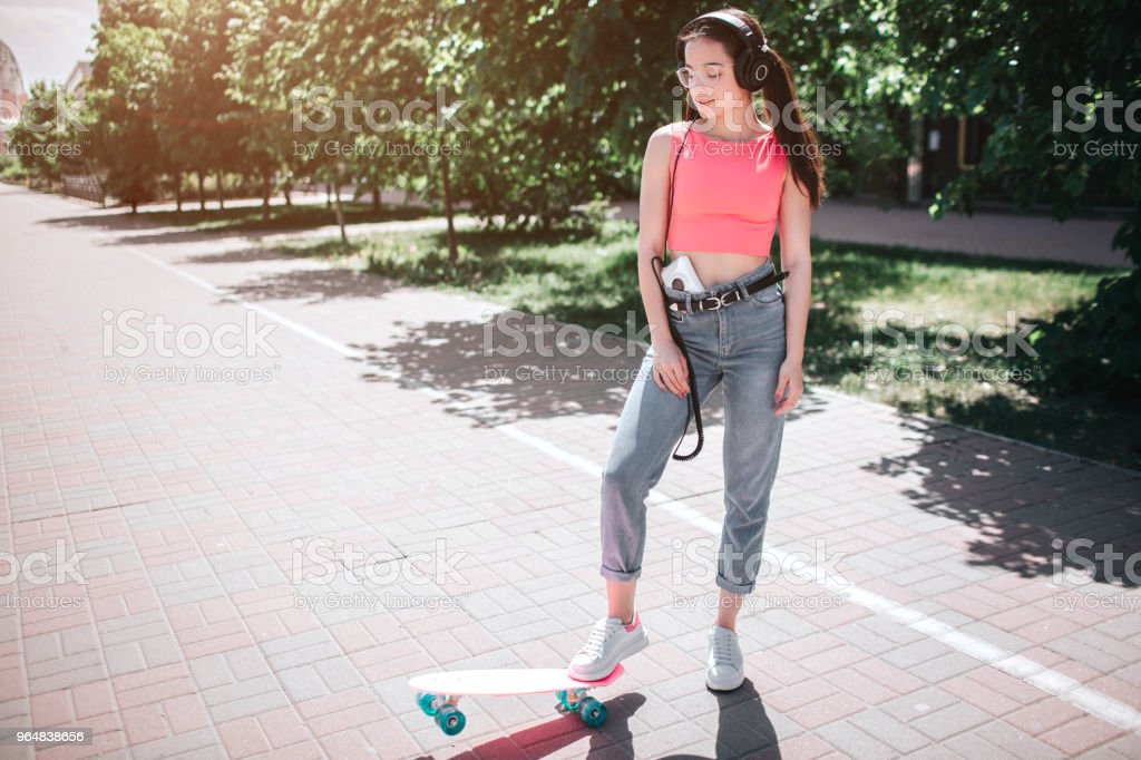 Beautiful and fantastic girl is standing on street in a sunny day and posing. She is holding one foot on skate. There is a music player in her pnats and heapsonhes on her head royalty-free stock photo
