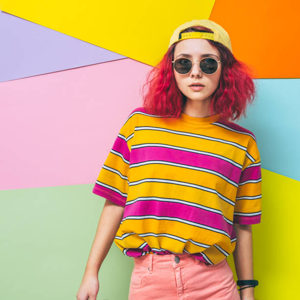 Beautiful and fashionable model with pink hair poses in striped t-shirt, sunglasses and yellow cap. Summer holidays concept. stock photo
