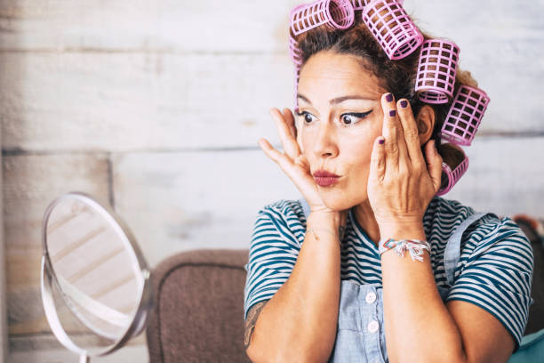 Beautiful and funny expression caucasian adult woman getting ready at home in front of the mirror with make up on the face - wrinkles checking and get older concept for young people - curlers on hair stock photo