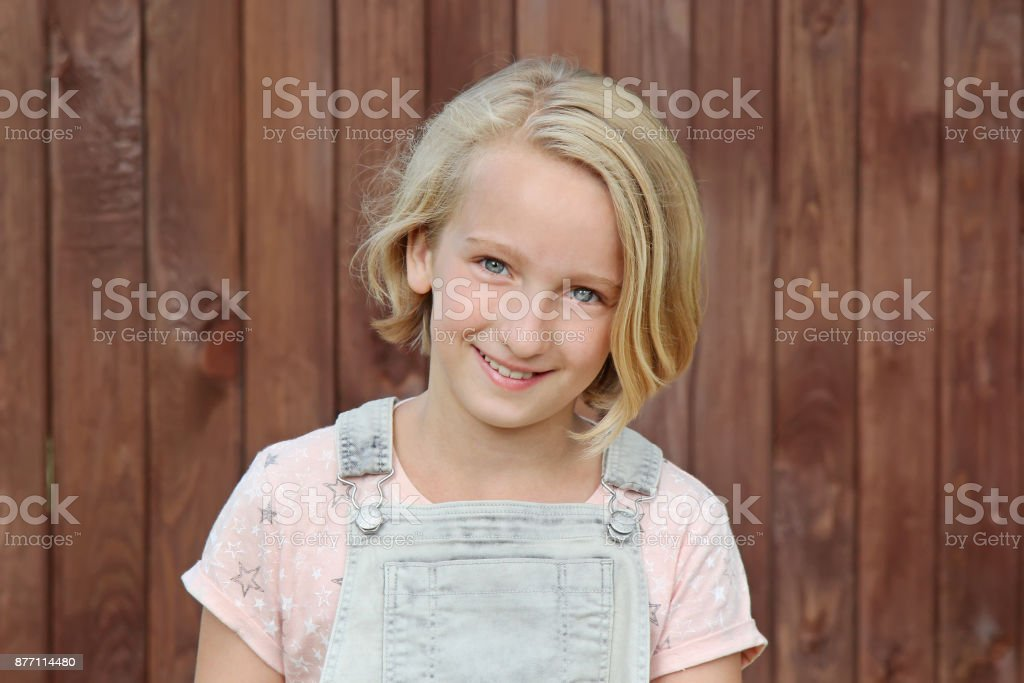 Beautiful and happy blonde girl smiles. Portrait on the background of a wooden wall. stock photo