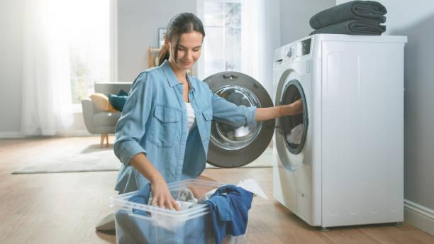 Schöne und glückliche Brünette junge Frau kommt auf die Waschmaschine in heimeligen Jeans Kleidung. Sie lädt die Waschmaschine mit schmutziger Wäsche. Helles und geräumiges Wohnzimmer mit modernem Interieur. – Foto
