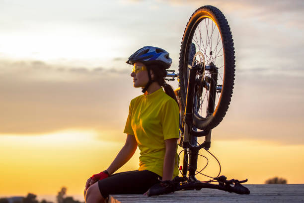 Beautiful and happy girl cyclist with a bike on nature. Healthy lifestyle and sports. Leisure and hobbies stock photo
