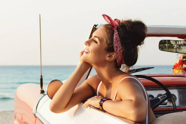 Beautiful and happy woman inside retro cabriolet car stock photo